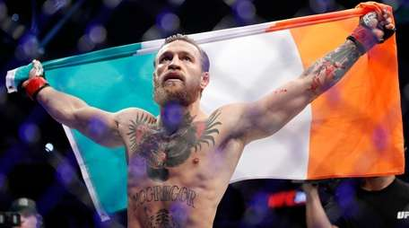 """Conor McGregor celebrates after defeating Donald """"Cowboy"""" Cerrone"""