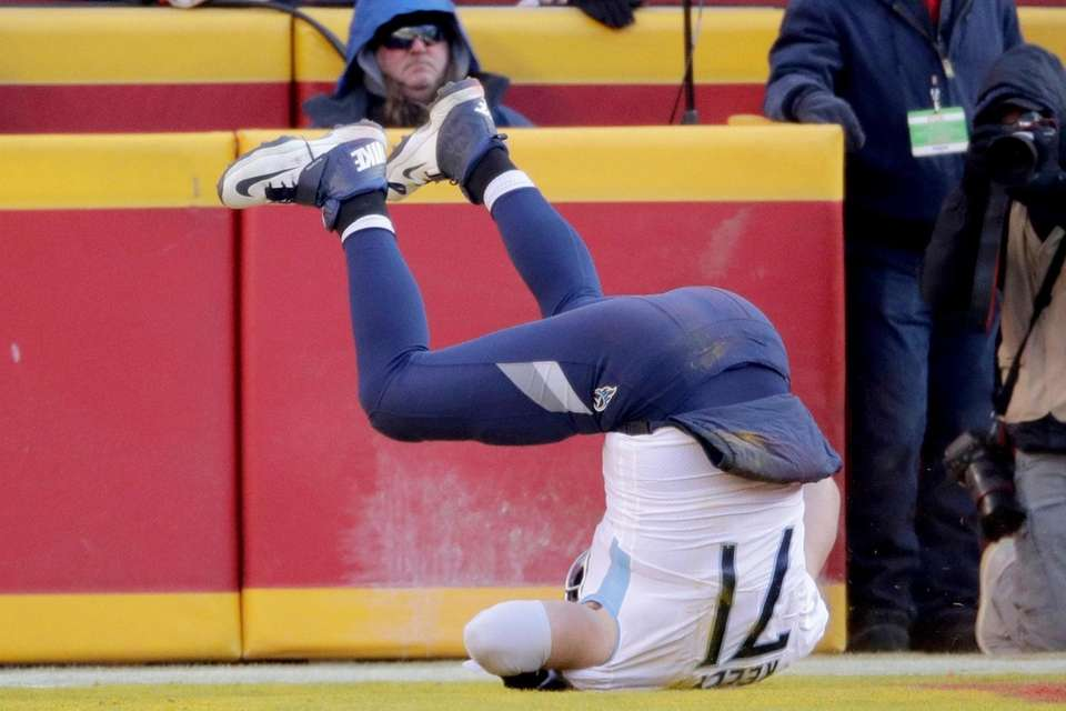Tennessee Titans' Dennis Kelly flips over as he