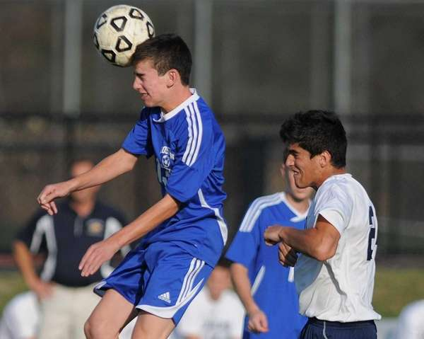Roslyn's Nick Markman, left, heads a ball away
