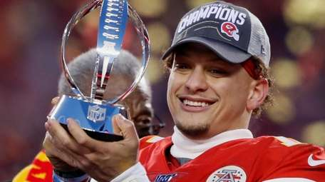The Chiefs' Patrick Mahomes holds up the Lamar