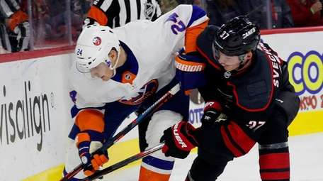 The Hurricanes' Andrei Svechnikov battles with the Islanders'