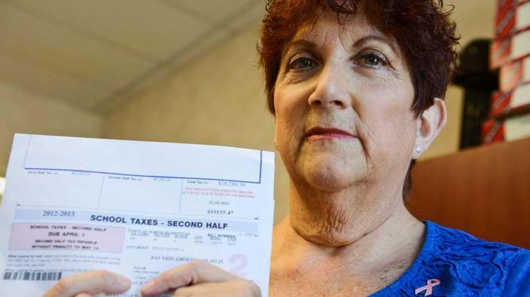 Leslie Spitzkoff stands with her tax bill inside