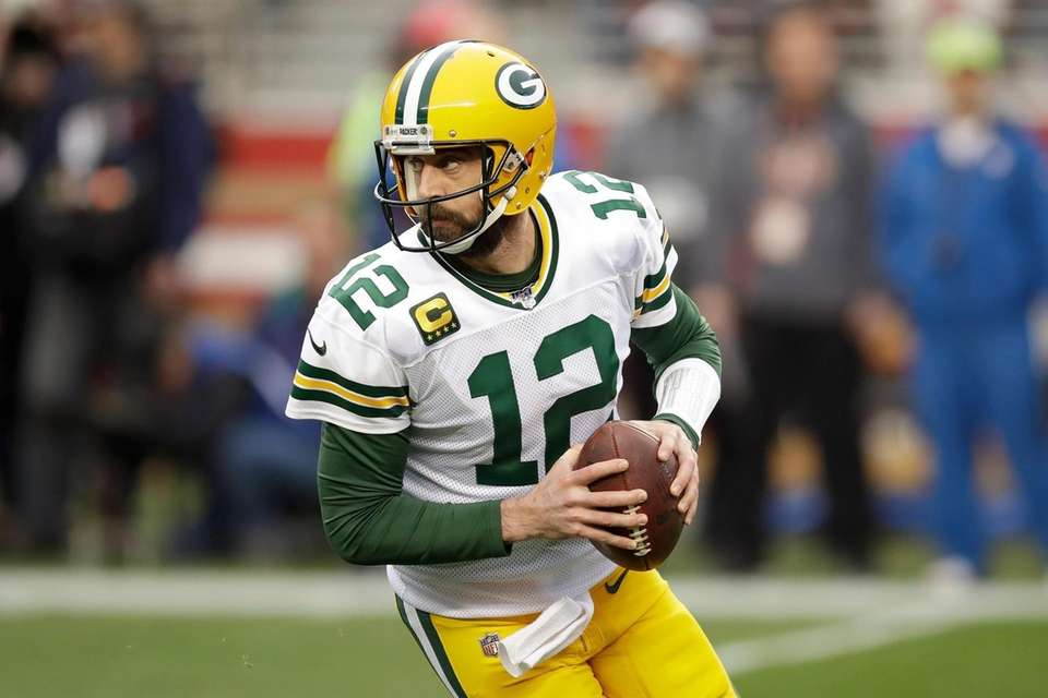 Green Bay Packers quarterback Aaron Rodgers rolls out