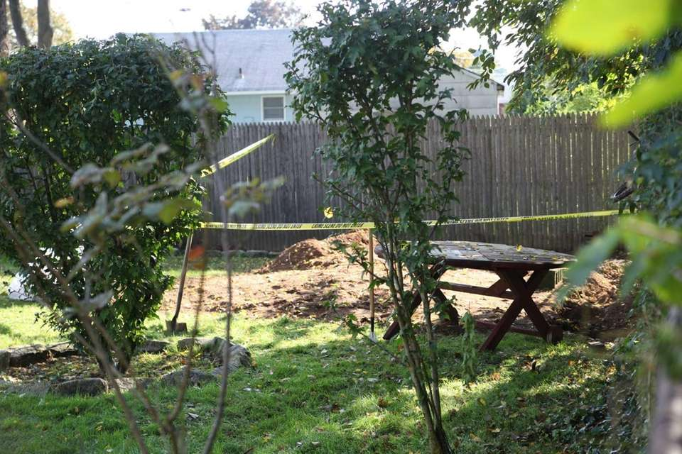 Police tape off an area in the backyard