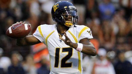 West Virginia quarterback Geno Smith looks for a