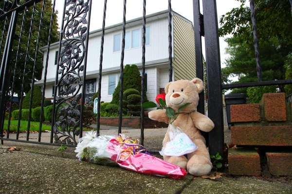 Flowers and a bear sat outside the gate,
