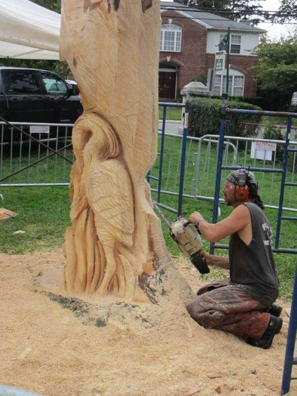 Sculptor Ken Packie carves up the trunk of