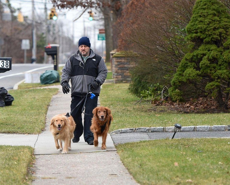 Jason Conelli, of Farmingville, walks with his golden