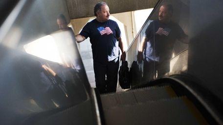 Guy Sini of Huntington rides the escalator at