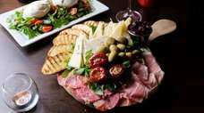 A charcuterie board for two with olives, peppers,