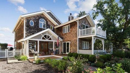 The wood-shingled house has a multi-level deck.