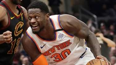 The Knicks' Julius Randle drives past the Cavaliers'