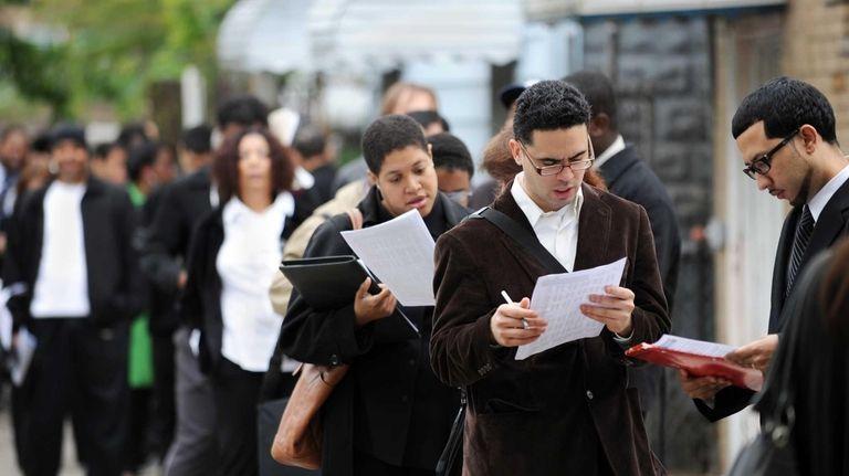 People seeking jobs wait in a line that