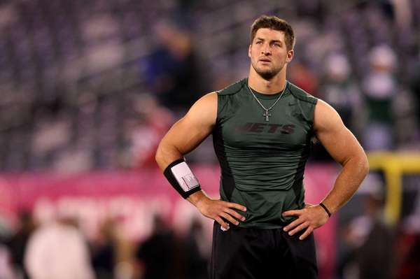 Tim Tebow looks on during warm-ups before a