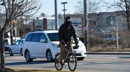 A man rides his bicycle along County Road