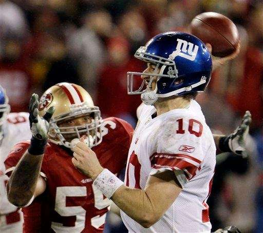 Eli Manning throws while being pressured by the