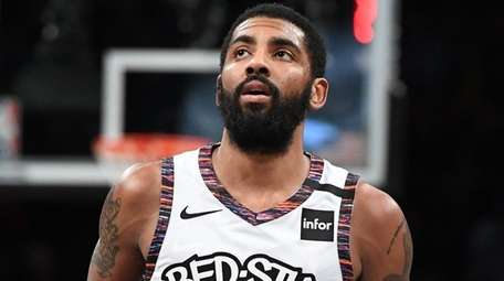 Nets guard Kyrie Irving looks on against the