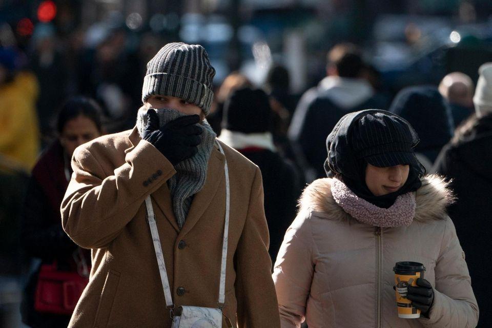 A bundled-up couple walk along Sixth Avenue, Manhattan,