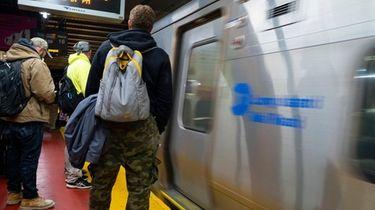 People wait to board a Long Island Rail