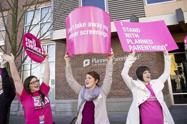 Planned Parenthood supporters hold up signs after a