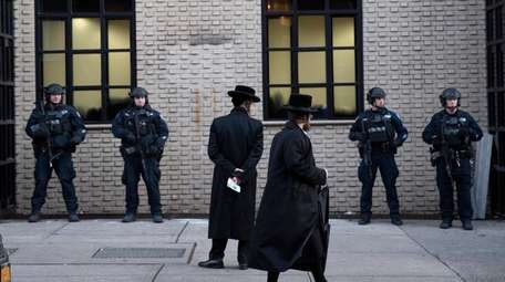 Orthodox Jewish men pass police guarding a Brooklyn