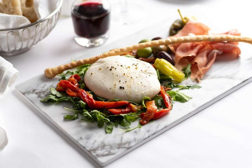 Burrata is served with marinated peppers, housemade rustico