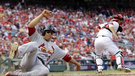 St. Louis Cardinals outfielder Carlos Beltran, left, slides