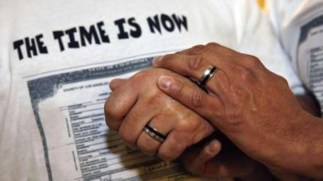 Two men hold hands after a bill allowing
