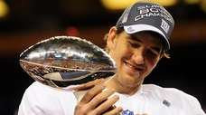 Giants quarterback Eli Manning holds aloft the VInce