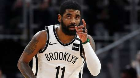 Nets guard Kyrie Irving reacts after a basket