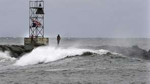 People fish in the rough surf on the