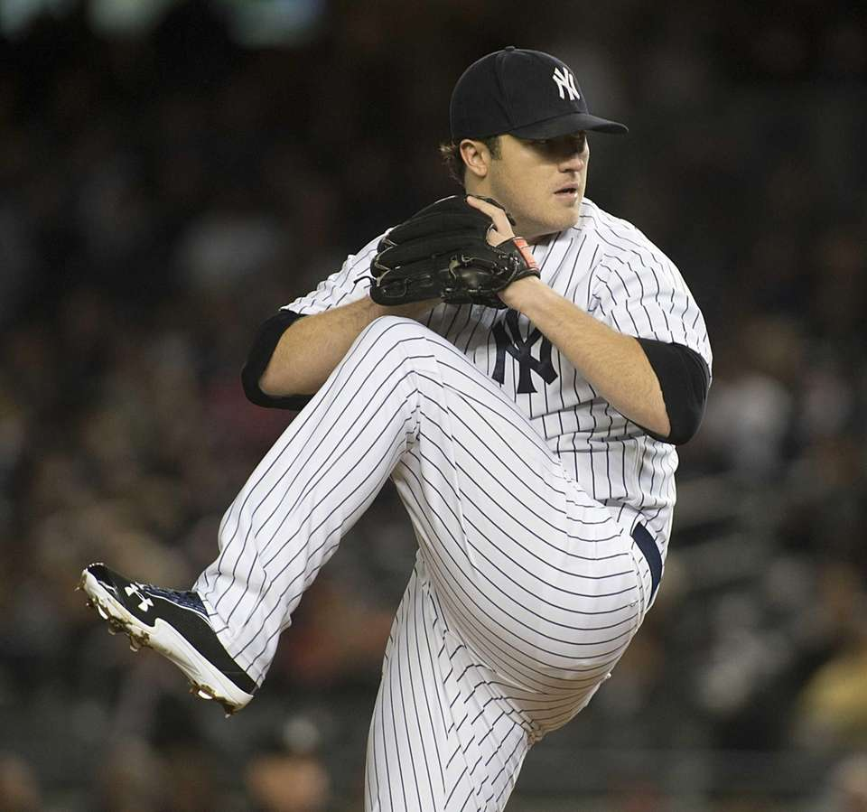 Yankees starting pitcher Phil Hughes delivers to the