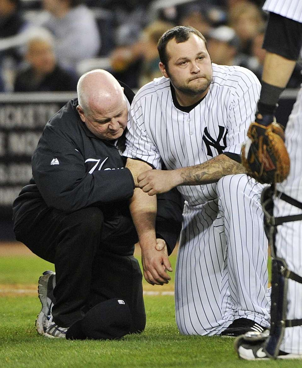 A trainer, left, helps Yankees relief pitcher Joba