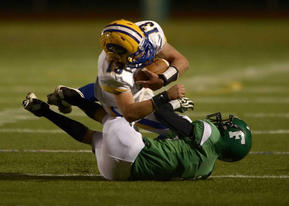 East Meadow's Chris Buschi dives over Farmingdale's Mike