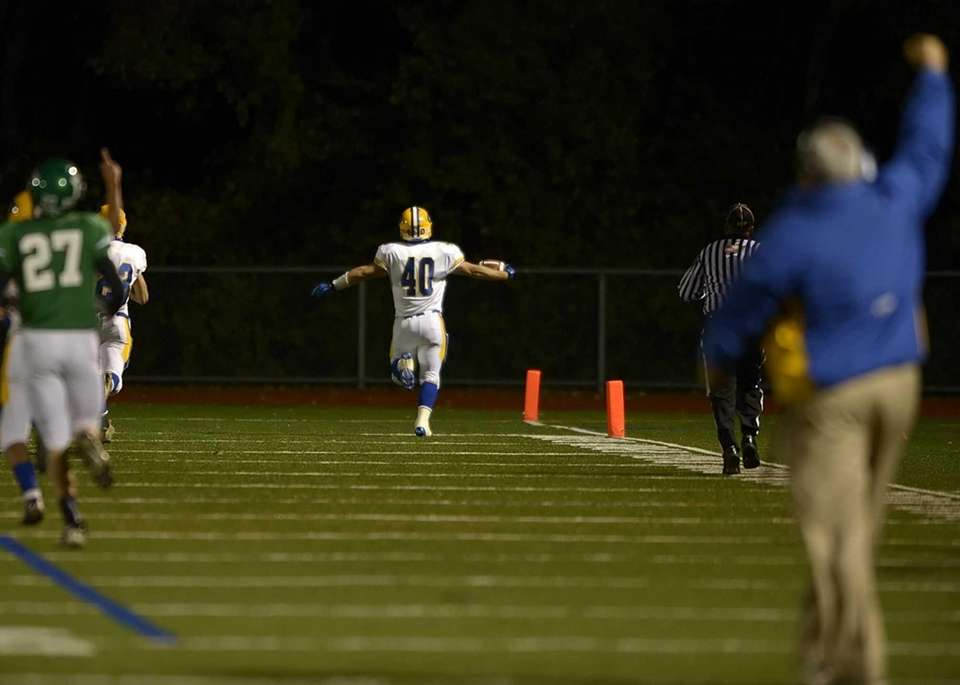 East Meadow's Billy Andrie runs back the fumbled