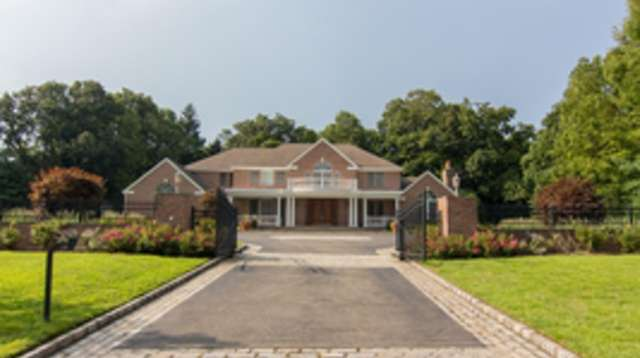 The gated entry follows a long paver driveway.