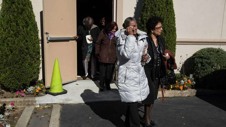 Mourners leave the funeral of Neal Rajapa, one