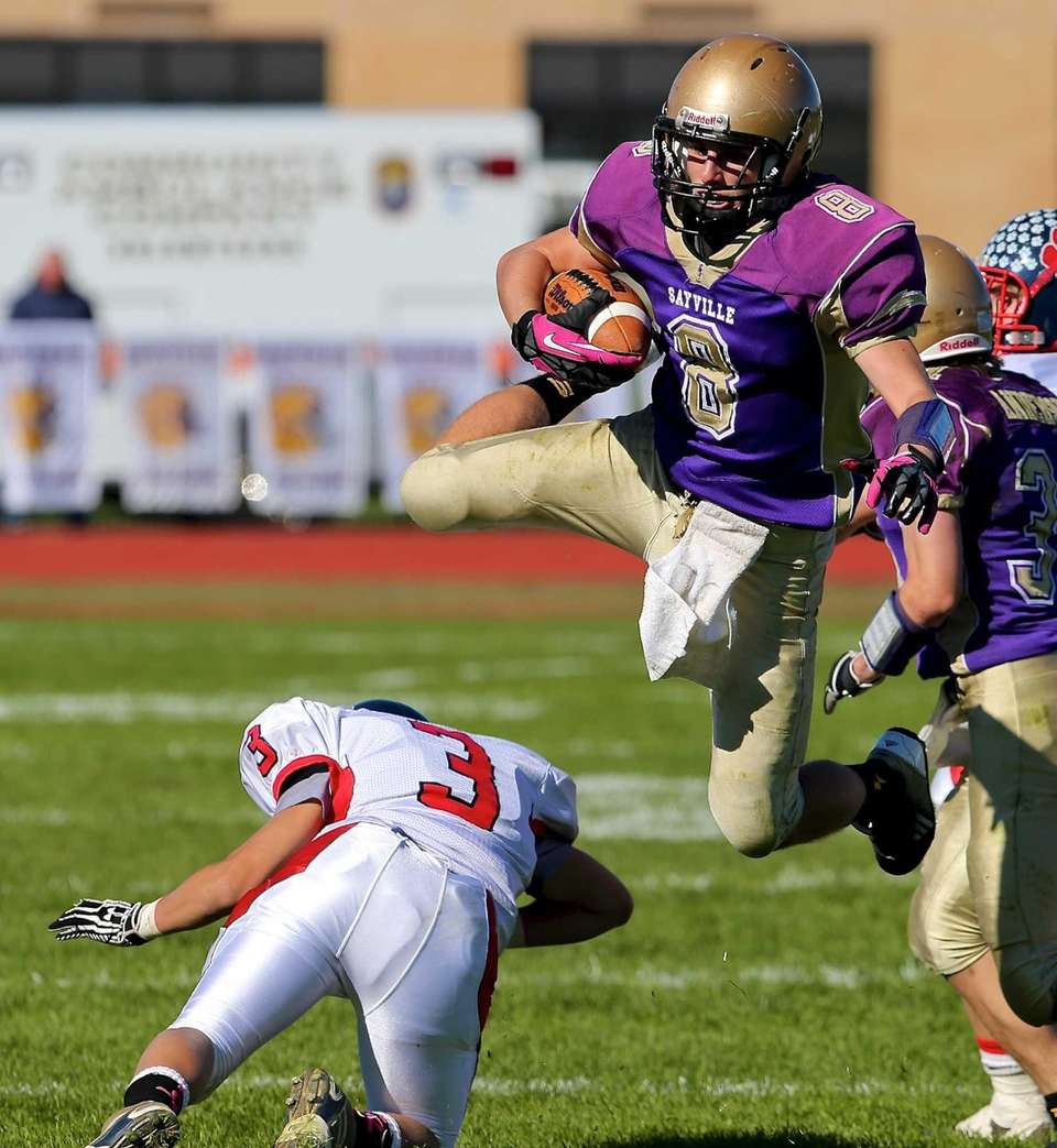 Sayville receiver Matthew Starr jumps over the attempted