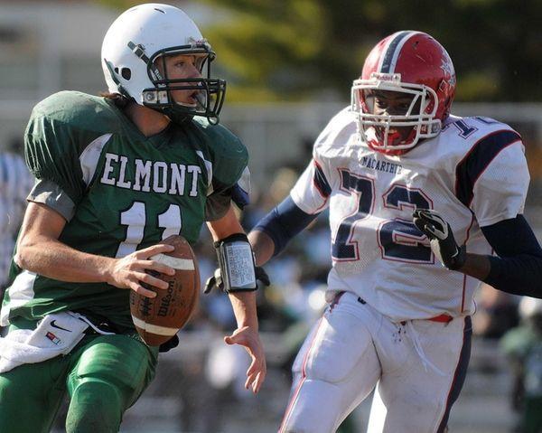 Elmont quarterback Michael Braun, left, evades MacArthur's Job