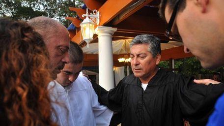 Ruben Cruzate, center, prays with members of his
