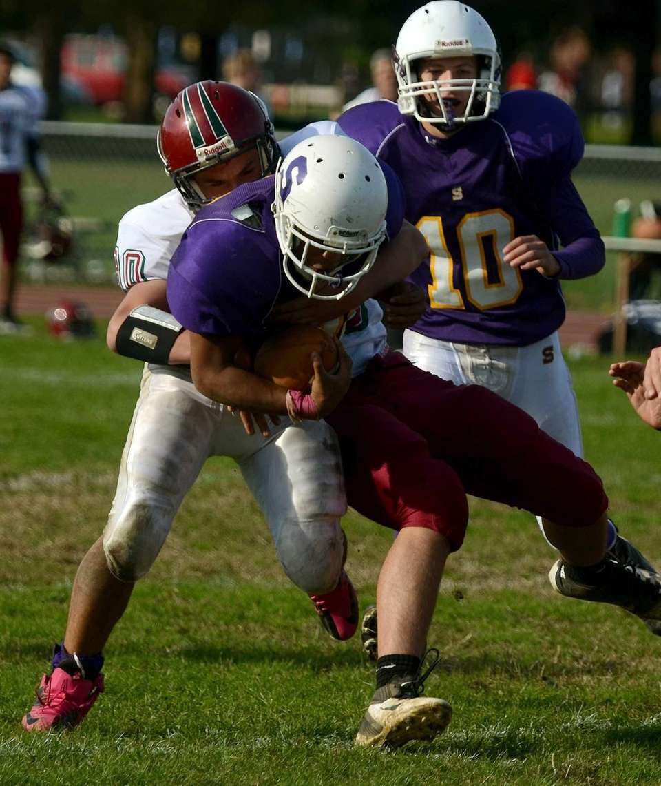 Sewanhaka's Diante Gonzalez is tackled by Glen Cove's