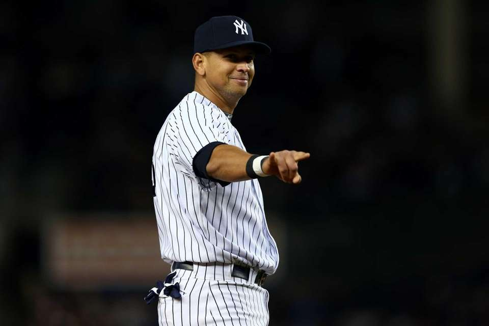 Alex Rodriguez gestures and smiles as he stands