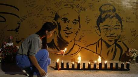 A fan lights a candle at a memorial