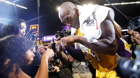 The Lakers' Kobe Bryant, right, fist-bumps his daughter