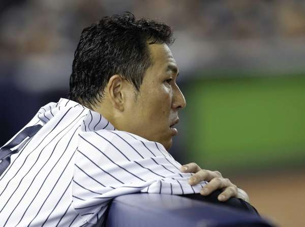 Hiroki Kuroda watches from the dugout during the