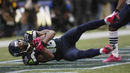 Seattle Seahawks' Sidney Rice comes down with a