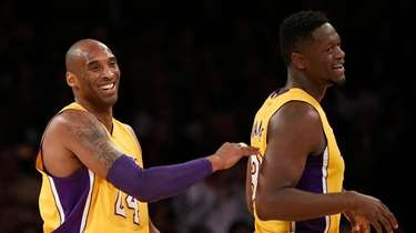 Kobe Bryant, left, celebrates with Julius Randle, right,