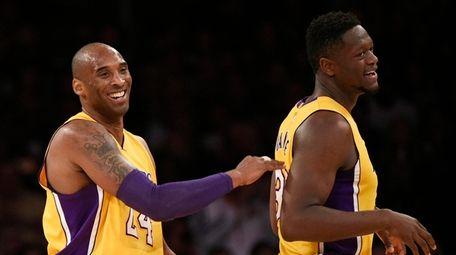 Kobe Bryant, left, celebrates with Julius Randle, right,