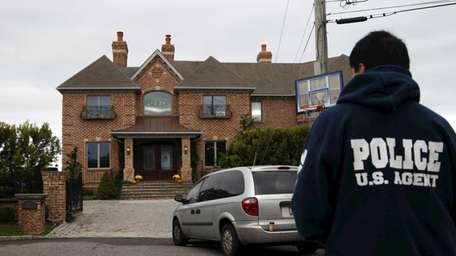 A law enforcement agent stands outside the home