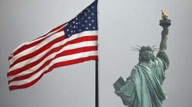 An America flag flies near the Statue of